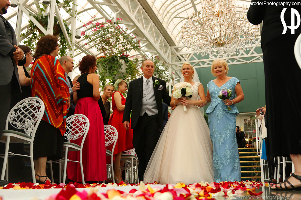 The bride enters the conservatory for the ceremony with her Dad and Mom